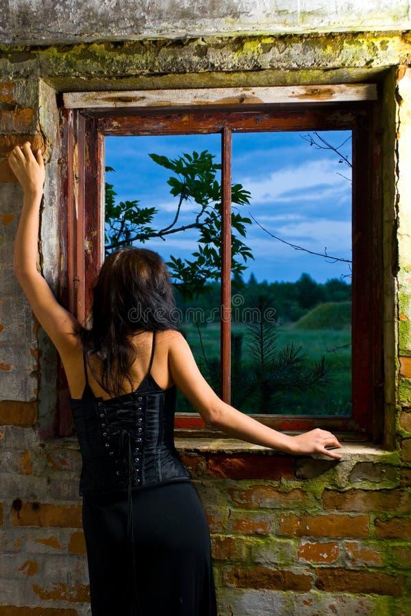 Mujer de Goth en la ventana imagen de archivo libre de regalías