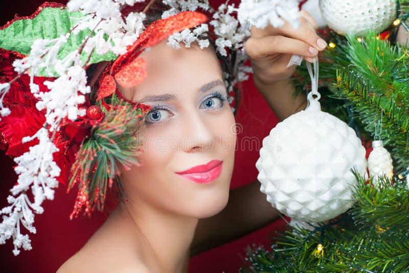 Mujer de hadas de la Navidad con el peinado del árbol que adorna el árbol de navidad fotografía de archivo