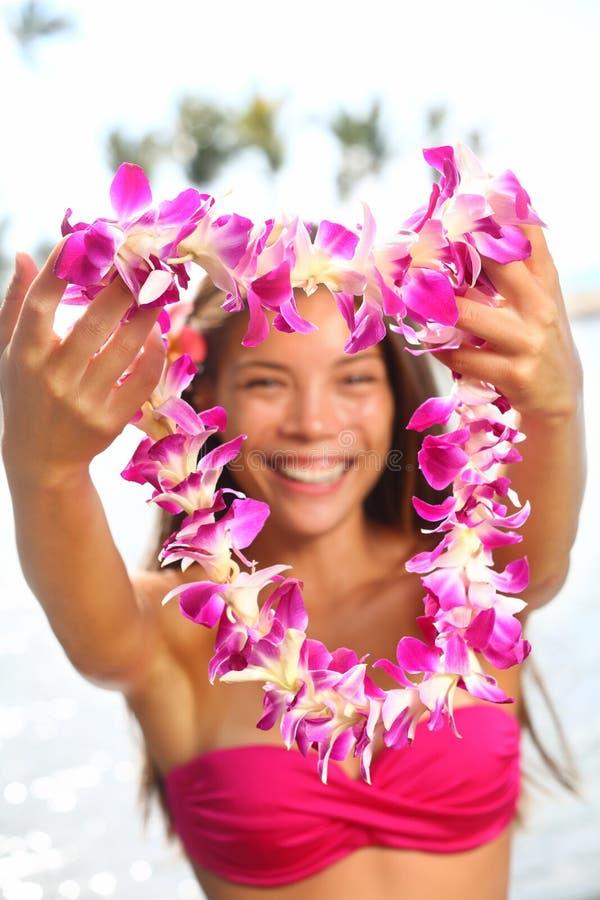 Mujer de Hawaii que muestra la guirnalda de los leus de la flor foto de archivo
