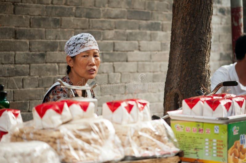 Mujer de Hui en una parada del mercado en la calle musulmán imagenes de archivo