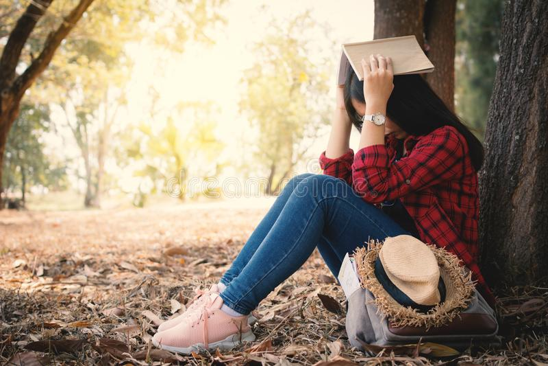 Mujer de la ansiedad sobre ella que estudia sentarse solo debajo del árbol grande en parque fotografía de archivo