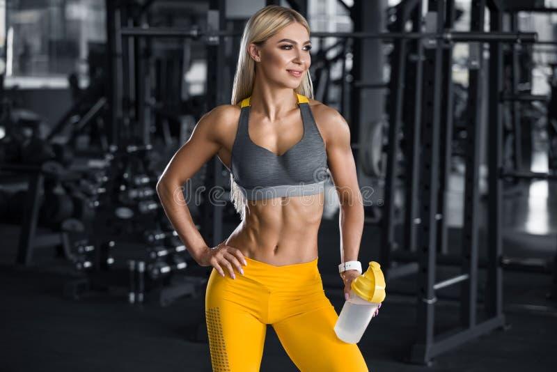 Mujer de la aptitud con la coctelera en el gimnasio, agua potable Muchacha atlética, cintura abdominal, delgada formada fotografía de archivo libre de regalías