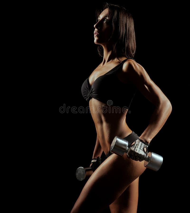 Mujer de la aptitud con el cuerpo perfecto que lleva a cabo pesas de gimnasia foto de archivo