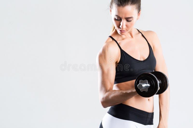 Mujer de la aptitud con un cuerpo hermoso que hace ejercicios con pesas de gimnasia aislada foto de archivo