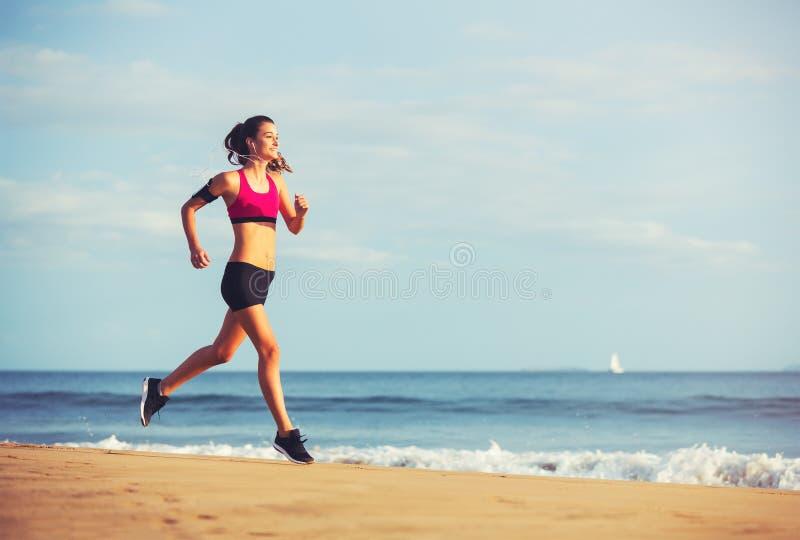 Mujer de la aptitud de los deportes que corre en la playa en la puesta del sol fotos de archivo