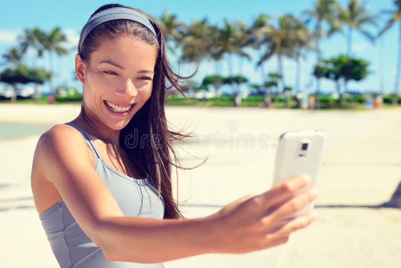 Mujer de la aptitud de Selfie en la playa con la célula del smartphone fotos de archivo
