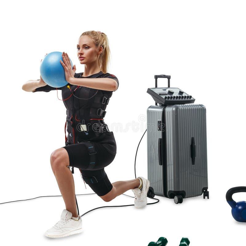 Mujer de la aptitud del ccsme que hace ejercicio de la estocada con la bola fotos de archivo