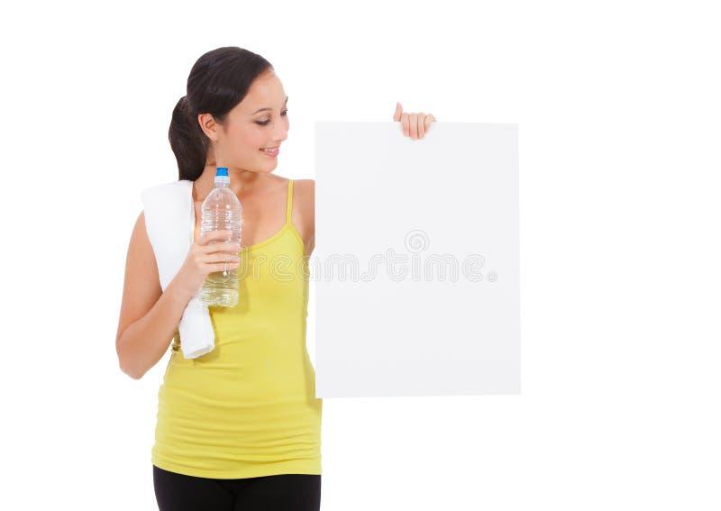 Mujer de la aptitud del deporte que sostiene la tarjeta vacía. imagen de archivo