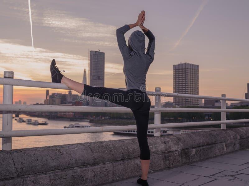 Mujer de la aptitud en actitud de la yoga en el puente en la salida del sol fotografía de archivo libre de regalías