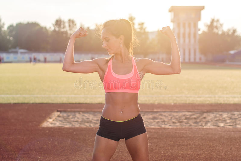 Mujer de la aptitud en el estadio que muestra apagado los brazos musculares que doblan bíceps fotos de archivo