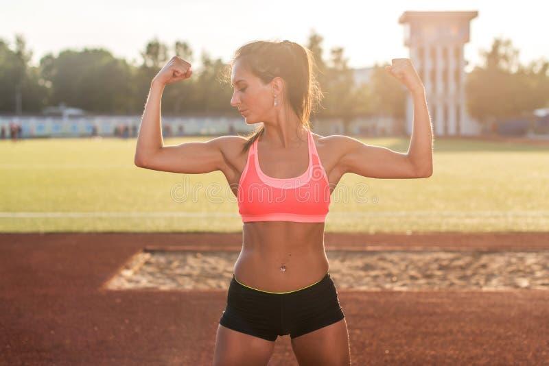 Mujer de la aptitud en el estadio que muestra apagado los brazos musculares que doblan bíceps fotos de archivo libres de regalías
