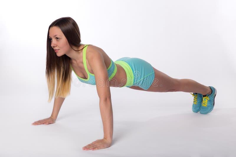 Mujer de la aptitud en el sporswear que hace ejercicios de la flexión de brazos foto de archivo