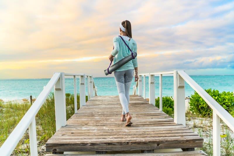 Mujer de la aptitud que camina con la estera de la yoga en la playa imagen de archivo