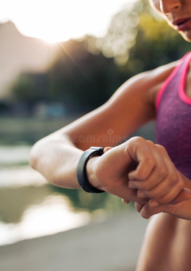 Mujer de la aptitud que comprueba su funcionamiento en smartwatch fotografía de archivo