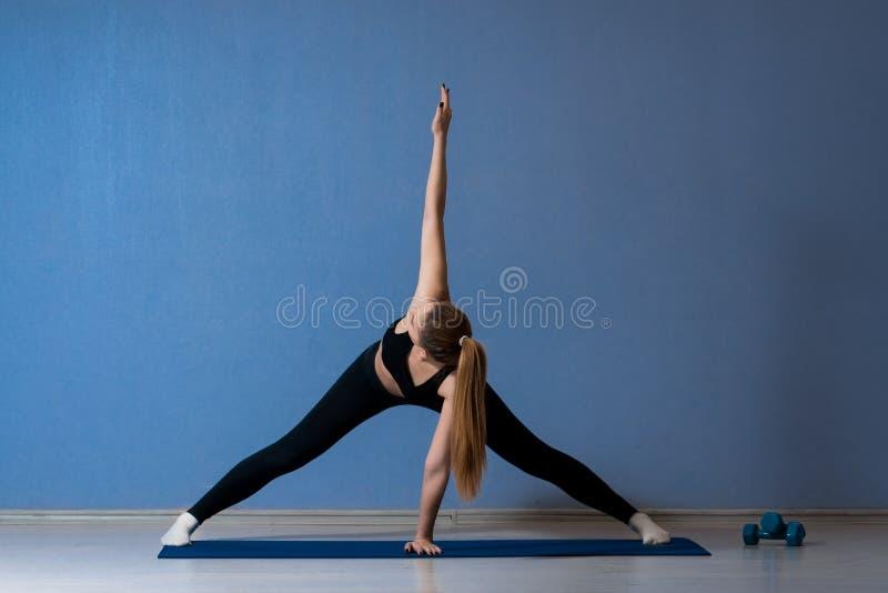 mujer de la aptitud que ejercita activamente en un estudio de la yoga imágenes de archivo libres de regalías