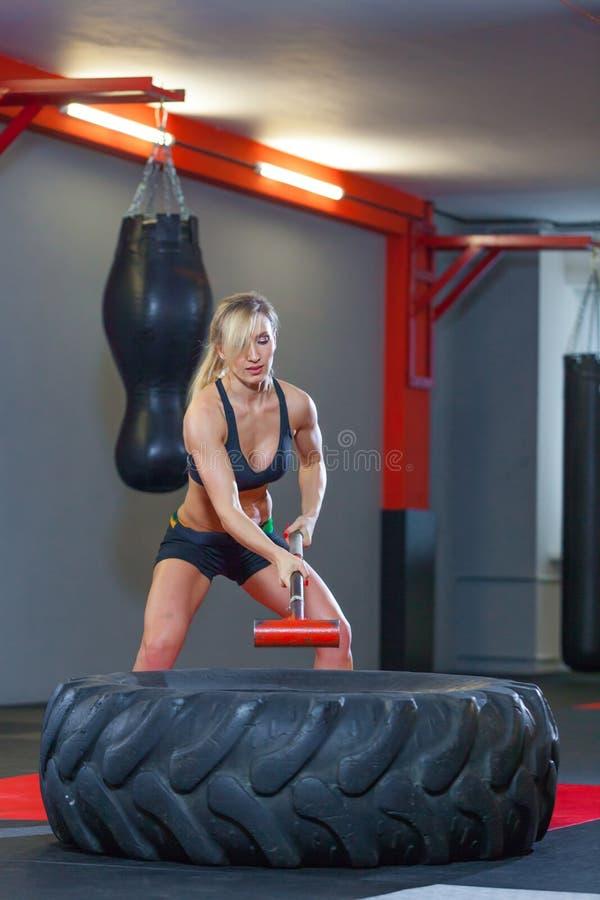 Mujer de la aptitud que golpea el neumático de la rueda con el trineo del martillo en el gimnasio foto de archivo libre de regalías