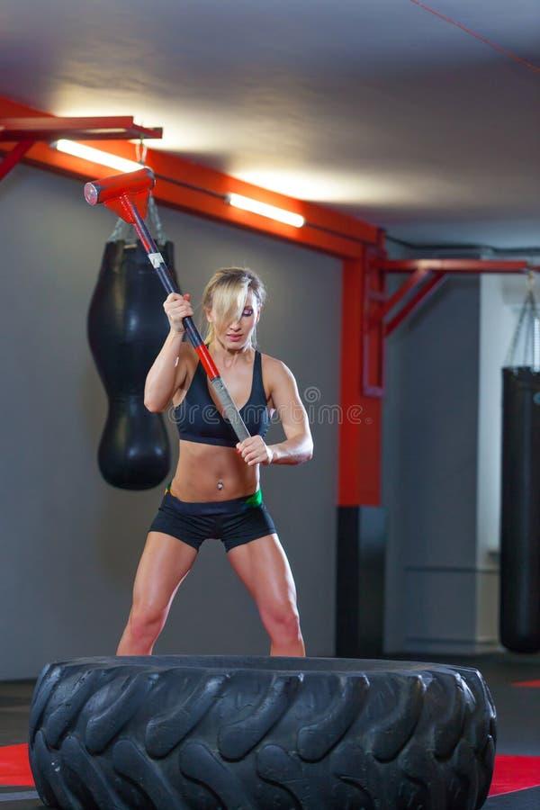 Mujer de la aptitud que golpea el neumático de la rueda con el trineo del martillo en el gimnasio imagen de archivo