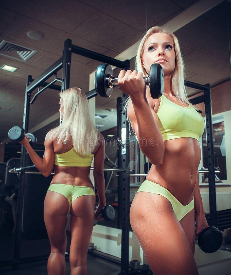 Mujer de la aptitud que hace ejercicios con pesa de gimnasia imagenes de archivo