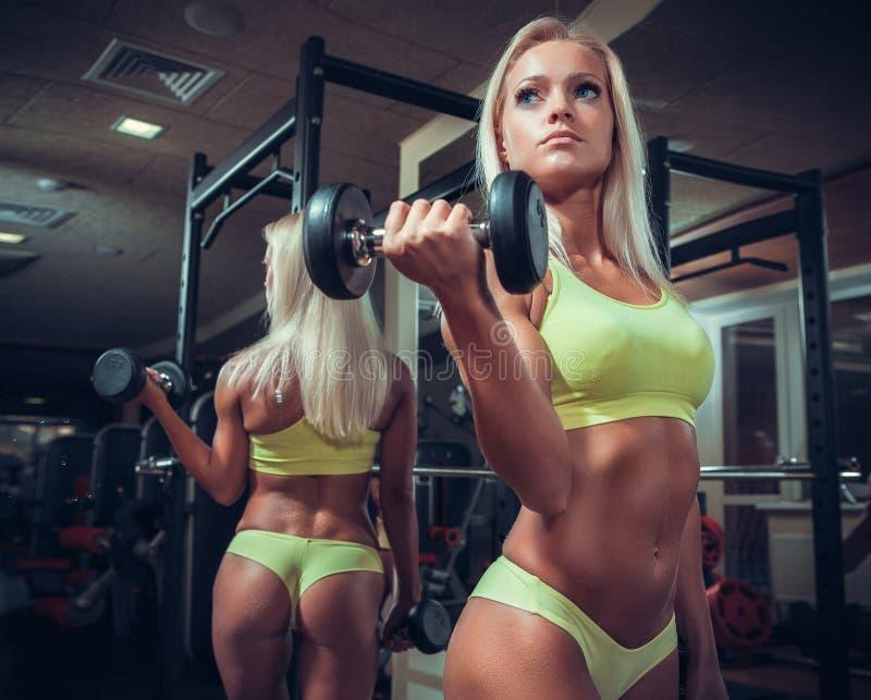 Mujer de la aptitud que hace ejercicios con pesa de gimnasia foto de archivo