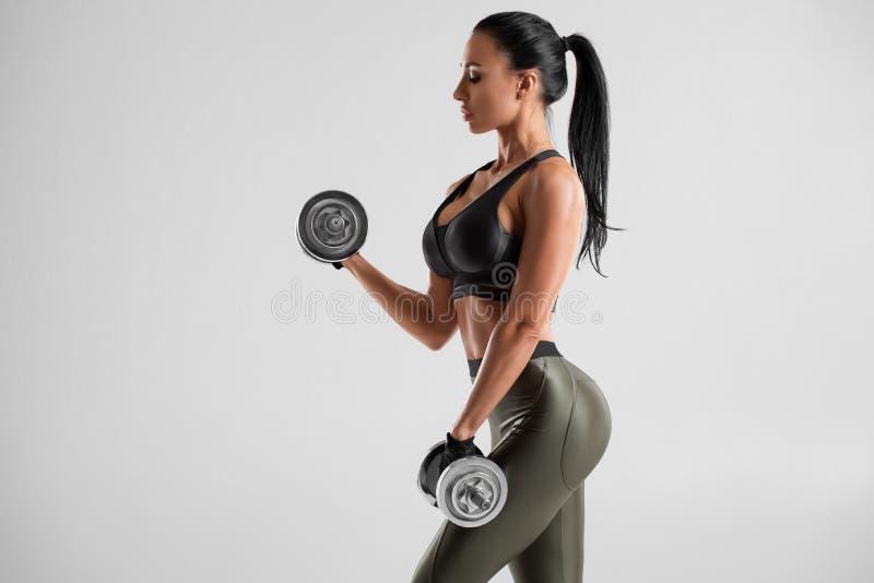 Mujer de la aptitud que hace el ejercicio para el b?ceps en fondo gris Entrenamiento muscular de la mujer con pesas de gimnasia imágenes de archivo libres de regalías
