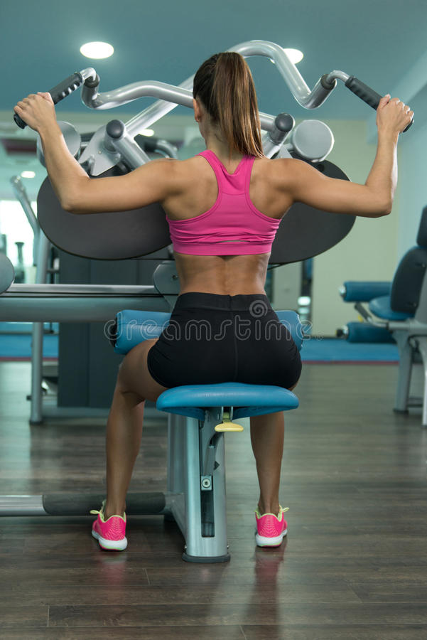 Mujer de la aptitud que hace el ejercicio para la parte posterior en la máquina imagenes de archivo
