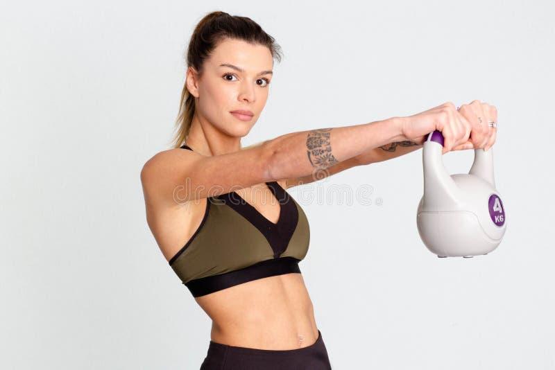 Mujer de la aptitud que hace entrenamiento apto cruzado con el kettlebell en la imagen de fondo blanca imagenes de archivo