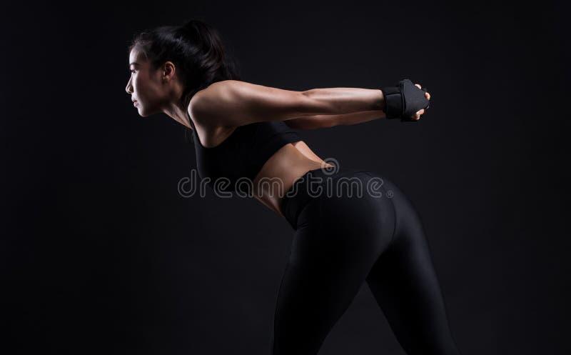Mujer de la aptitud que hace estirando entrenamiento en negro foto de archivo libre de regalías