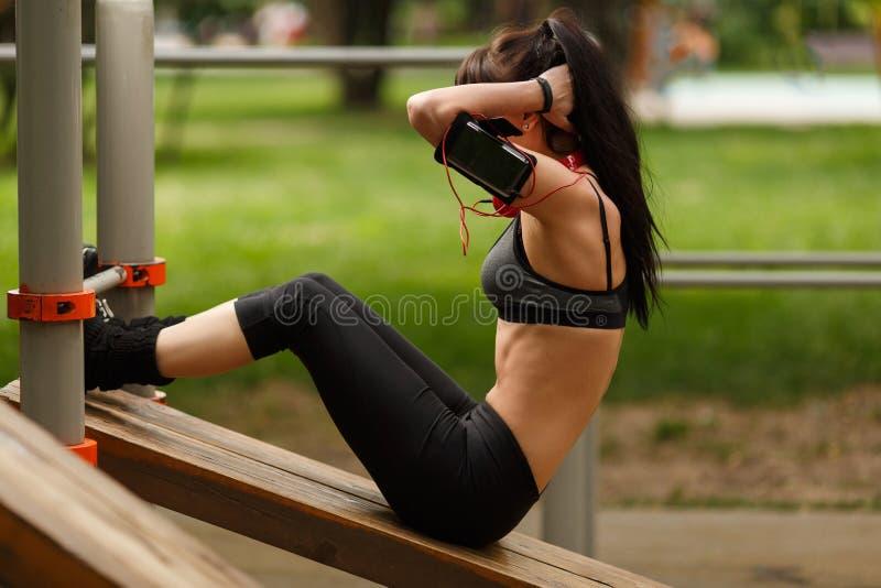 Mujer de la aptitud que hace sentar-UPS que ejercita para sus músculos abdominales imagen de archivo