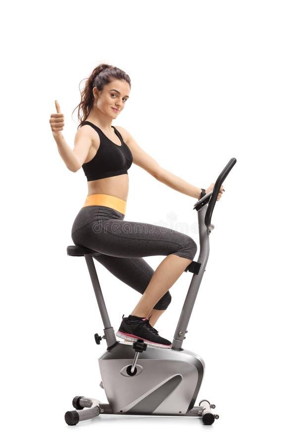 Mujer de la aptitud que monta una bicicleta estática y que hace un pulgar encima de la muestra imagen de archivo