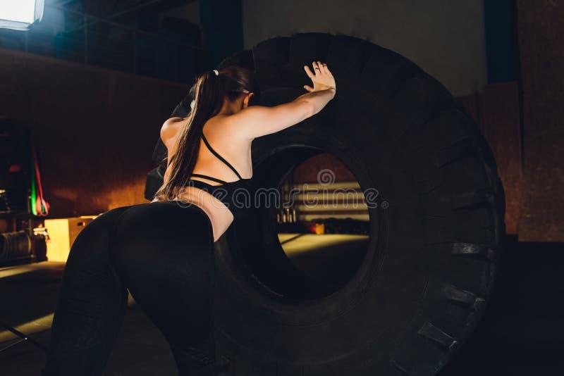 Mujer de la aptitud que mueve de un tir?n el neum?tico de la rueda en gimnasio Atleta de sexo femenino apto que se resuelve con u fotos de archivo