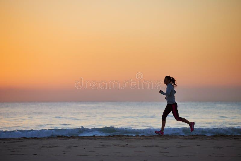 Mujer de la aptitud que se ejecuta en la playa imagen de archivo libre de regalías