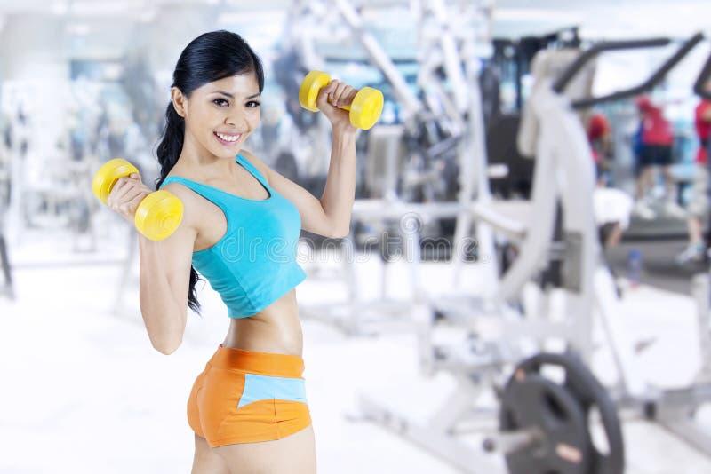 Mujer de la aptitud que se resuelve con pesas de gimnasia foto de archivo libre de regalías