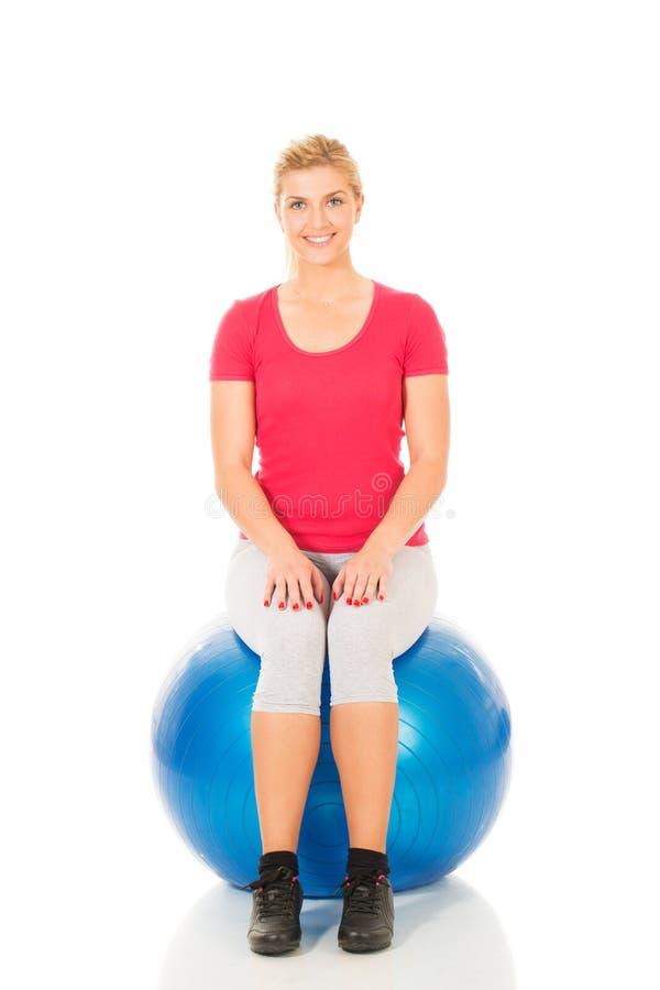 Mujer de la aptitud que se sienta en bola de los pilates foto de archivo