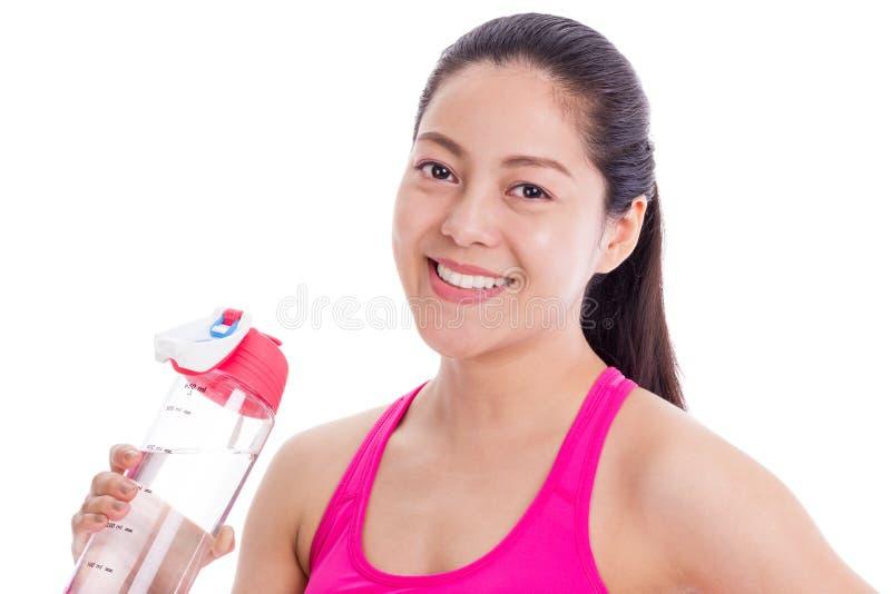 Mujer de la aptitud que sonríe y que sostiene la botella de agua Aislado en pizca foto de archivo