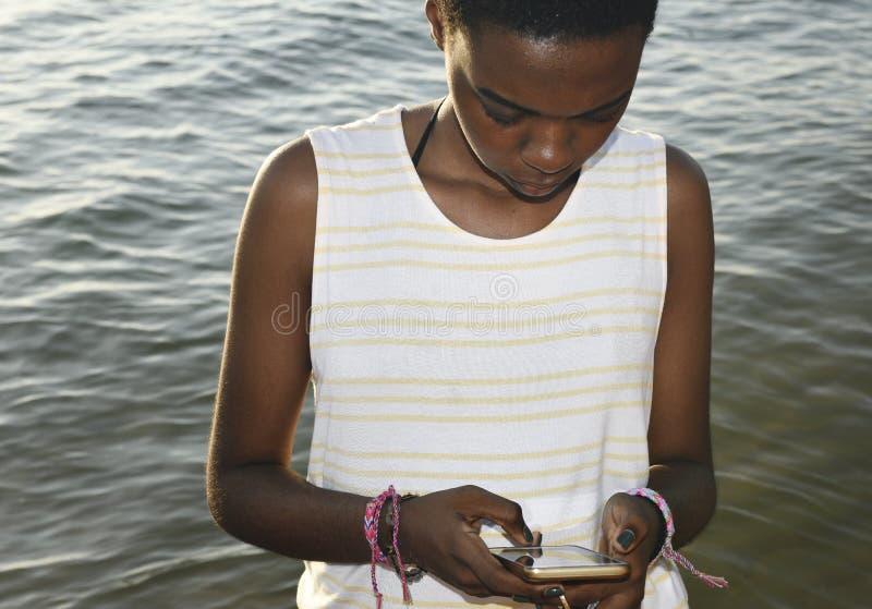 Mujer de la ascendencia africana que usa el teléfono móvil por el mar foto de archivo