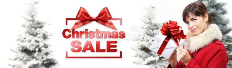 Mujer de la bandera de la venta de la Navidad con la caja de regalo en los wi blancos del fondo fotografía de archivo