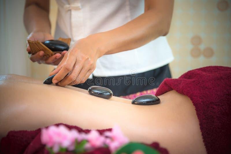 Mujer de la belleza de Asia que se acuesta en cama del masaje con el alon caliente de las piedras del balinese tradicional foto de archivo
