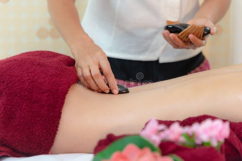 Mujer de la belleza de Asia que se acuesta en cama del masaje con las piedras calientes del balinese tradicional a lo largo de la imágenes de archivo libres de regalías