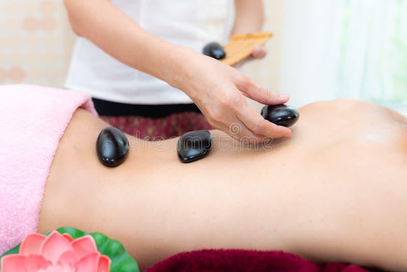 Mujer de la belleza de Asia que se acuesta en cama del masaje con las piedras calientes del balinese tradicional a lo largo de la fotos de archivo libres de regalías