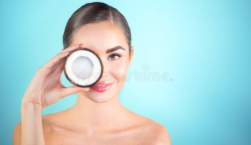 Mujer de la belleza con el coco Muchacha morena joven bonita que celebra la nuez y la sonrisa de los Cocos Balneario y skincare fotografía de archivo libre de regalías