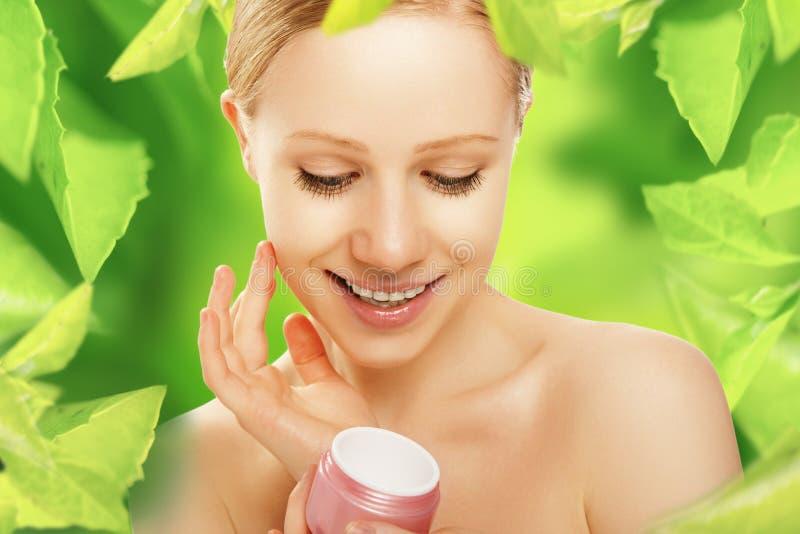 Mujer de la belleza con el cuidado de piel poner crema y natural en verde foto de archivo libre de regalías