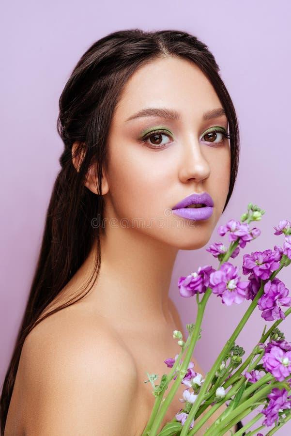 Mujer de la belleza con las flores magentas de la orqu?dea de la corona floral imagen de archivo