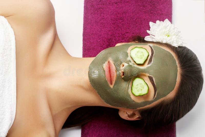 Mujer de la belleza con la máscara facial de la arcilla y pepinos en ojos en balneario de la belleza foto de archivo