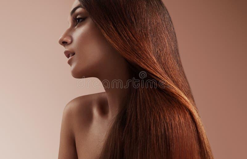 Mujer de la belleza con un pelo recto sano foto de archivo