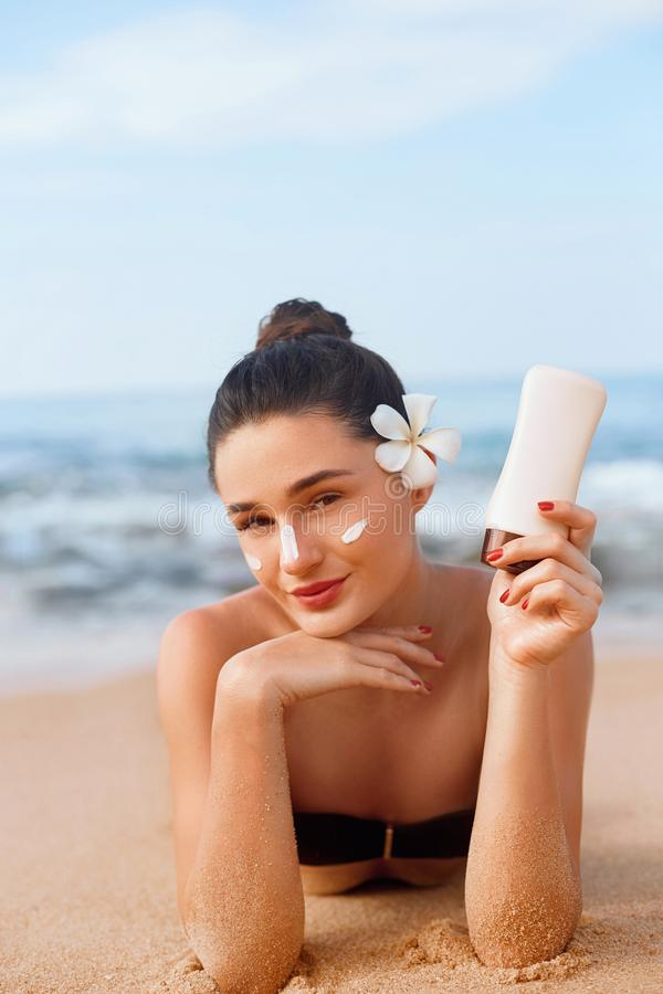 Mujer de la belleza en el bikini que sostiene las botellas de protección solar en sus manos Skincare Una crema de aplicación feme fotografía de archivo libre de regalías
