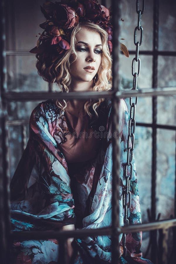 Mujer de la belleza en el palacio Muchacha elegante de la moda lujosa en jaula Vestido de la flor y una guirnalda de flores imagenes de archivo