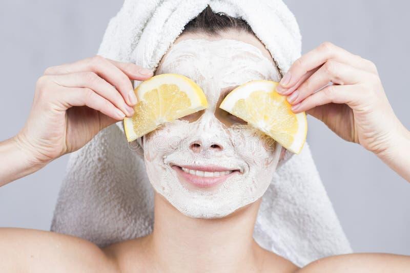 Mujer de la belleza que consigue la máscara facial Mujer joven atractiva con la máscara de la fruta en cara en el salón del balne imagen de archivo libre de regalías