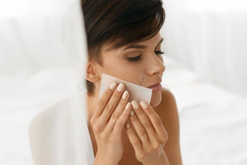 Mujer de la belleza que limpia la piel fresca hermosa con el tejido absorbente imagen de archivo