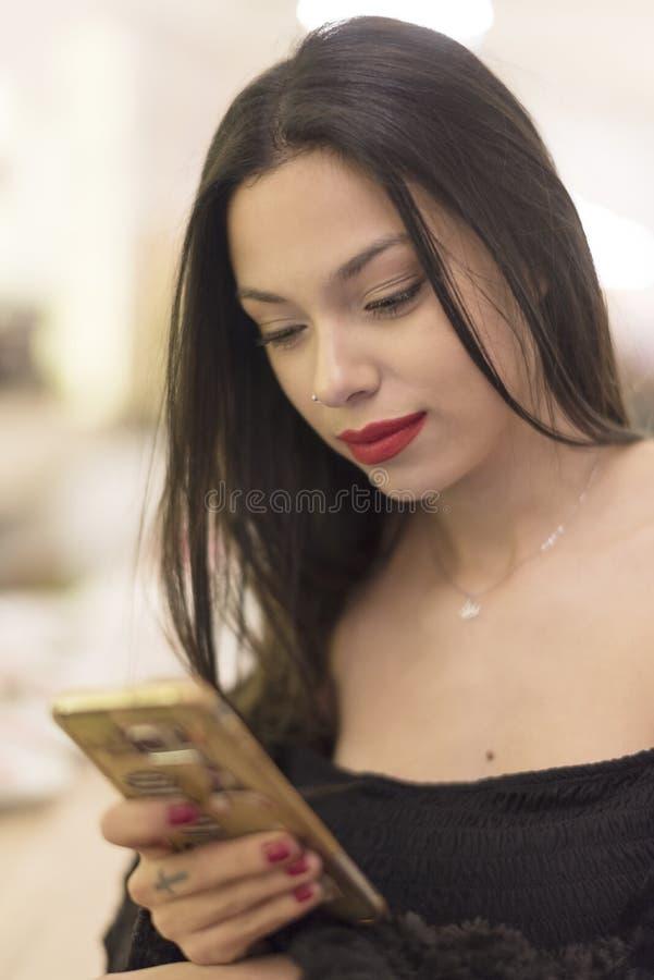 Mujer de la belleza que mira smartphone en barra fotos de archivo