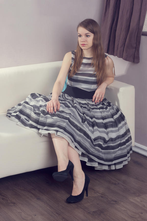 Mujer de la belleza que se sienta en el sofá imagen de archivo